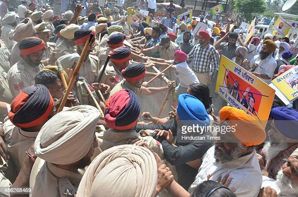 Police try to stop the family members of 1984 AntiSikh riots victims try to break a barricade during a protest against the Congress Lok Sabha...