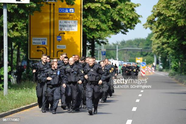 A police unit walks near the venue of a party congress of Germany's farright and antiimmigration party AfD in Augsburg southern Germany on June 30...