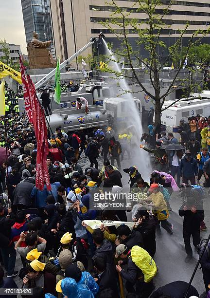 Police use a water cannon during clashes with South Korean protestors at a rally to commemorate the first anniversary of the Sewol ferry disaster in...