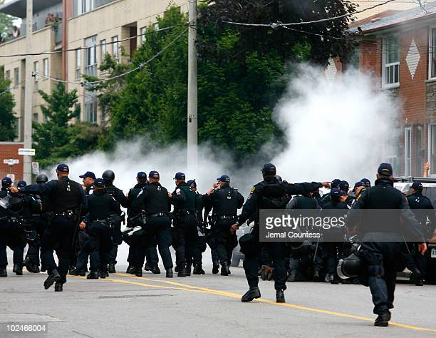 Police use smoke bombs to disperse protestors at a rally outside the temporary G20 police detention center where over 500 people are now being...