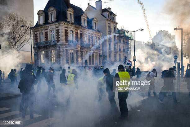 Police use tear gas as members of the yellow vest takes part in the 15th consecutive Saturday of demonstrations in Rennes western France on February...