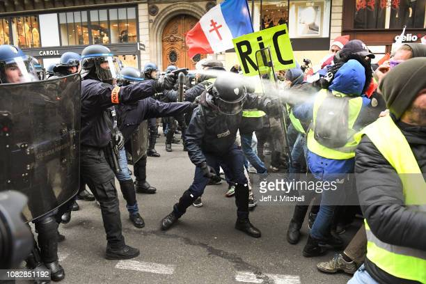 Police use tear gas on Protesters holding a placard with the letters RIC Referendum d'Initiatives Citoyennes as they gather at Place de l' Opera...