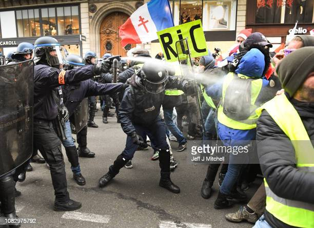 """Police use tear gas on Protesters holding a placard with the letters """"RIC"""" Referendum d'Initiatives Citoyennes as they gather at Place de l' Opera..."""