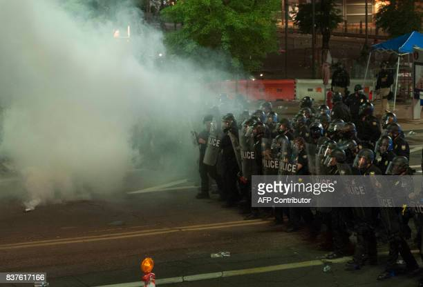 Police use tear gas to break up protesters gathered outside of the Phoenix, Arizona, Convention Center where US President Donald Trump spoke at a...