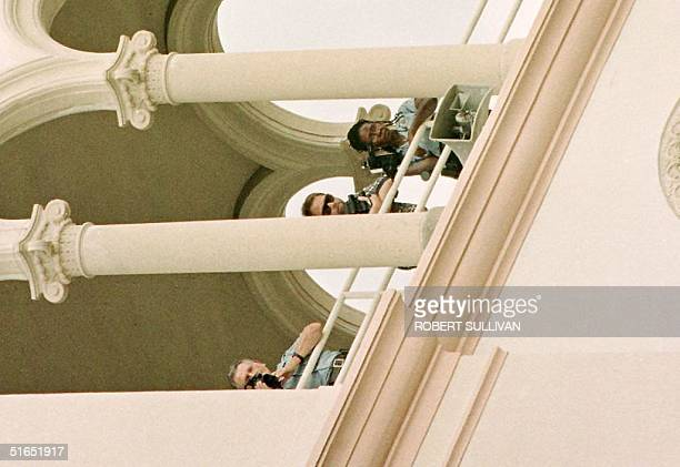 Police use video cameras to record the arrival of mourners for a memorial service for slain Italian designer Gianni Versace 18 July at St Patrick's...