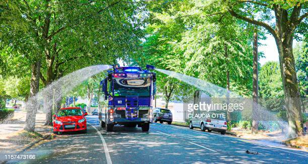 Police uses a water cannon to irrigate roadside trees on July 24 2019 in Wuppertal western Germany where temperatures reached 35 degrees Celsius...