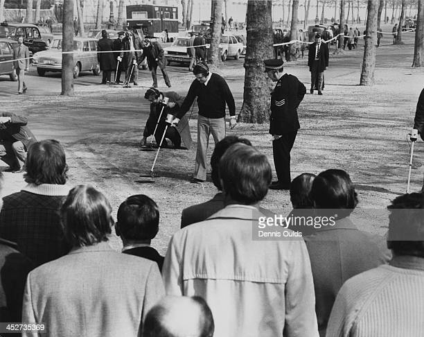 Police using metal detectors search for spent cartridges and other evidence in a cordoned-off area of the Mall, London, 21st March 1974. The search...