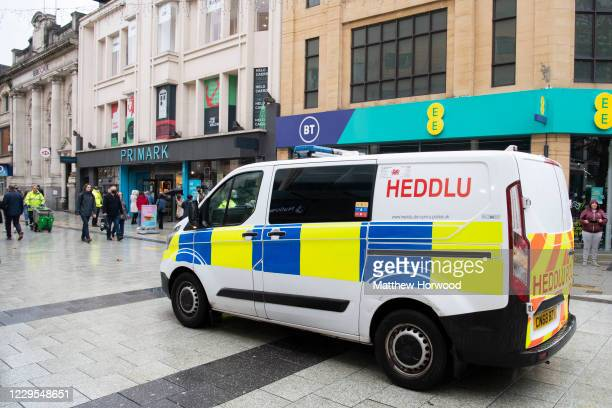 Police van drives down Queen Street on November 9, 2020 in Cardiff, Wales. Wales' health minister said cases are levelling off after its 17-day...