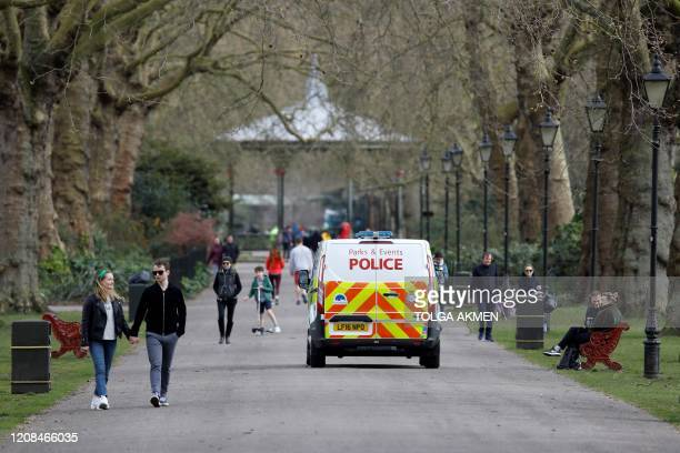 A police van drives pas people taking their daily exercise allowance in Battersea Park in London on March 28 as life in Britain continues during the...