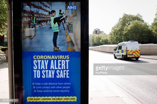 Police van drives past government messaging to 'Stay Alert', the core slogan of its new covid-19 prevention campaign, at a bus stop at Hyde Park...