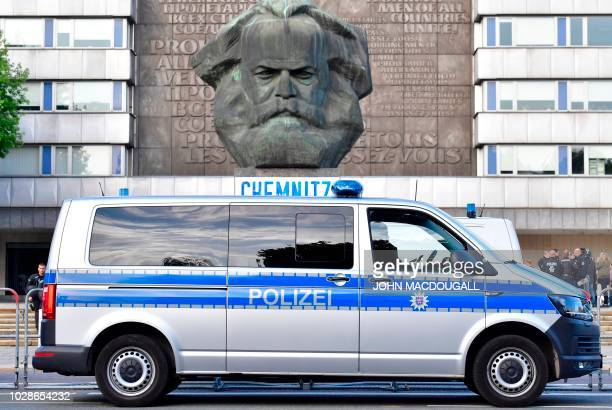"""Police van is parked in front of the city's Karl Marx monument during a gathering of the right-wing populist """"Pro Chemnitz"""" movement on September 7,..."""