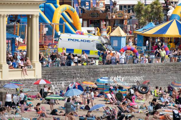 A police van on the promenade as people gather on the beach at Whitmore Bay Barry Island on August 7 in Barry Wales Forecasters have said Friday...
