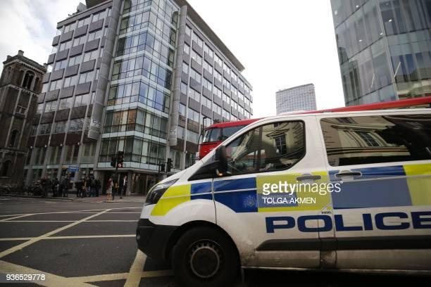 A police van passes the shared building which houses the offices of Cambridge Analytica in central London on March 22 as an alert for a suspicious...