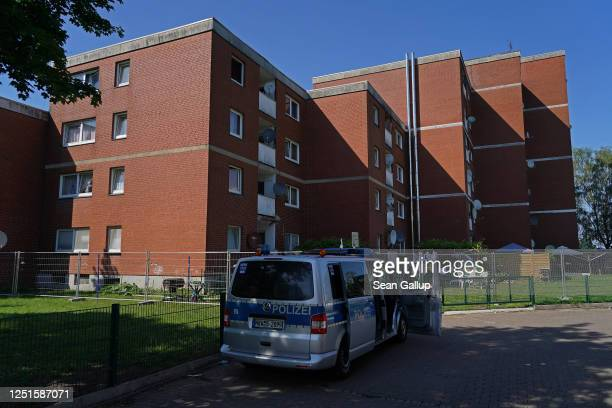 Police van stands outside an apartment building that houses workers from the nearby Toennies meat packing plant who are under quarantine in the town...