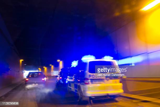 police van with blue lights chasing car in tunnel - chasing stock pictures, royalty-free photos & images