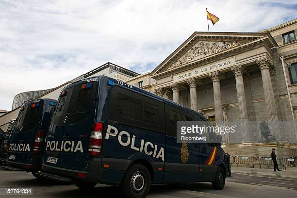 Police vans are parked outside the Spanish parliament building before a march organized to protest against the government's austerity measures in the...