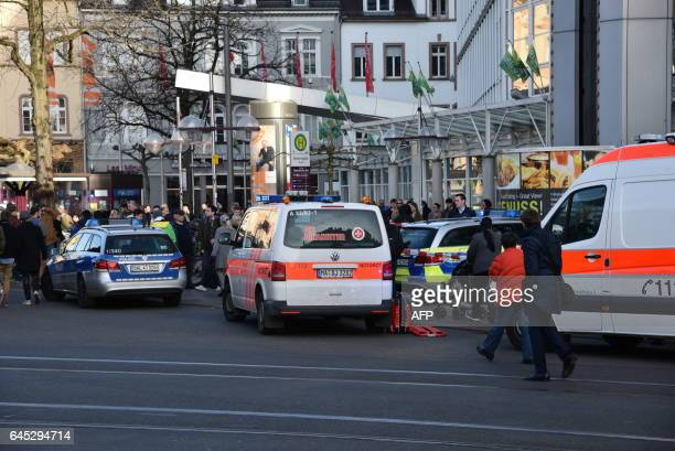 Police vehicle and ambulance stand in front of a business building in Heidelberg western Germany where a man ploughed into pedestrians on February 25...