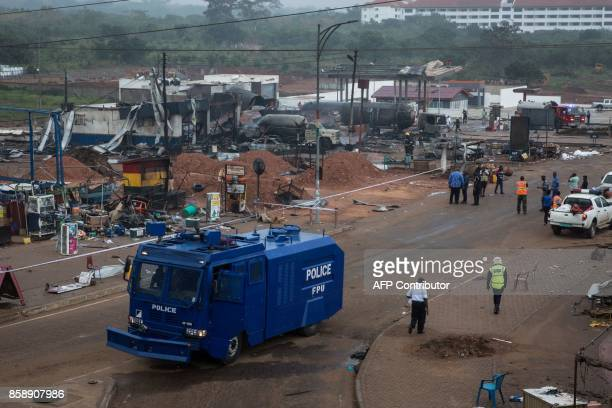 A police vehicle drives on the site of an explosion in Accra on October 8 2017 a day after a gas tanker caught fire triggering explosions at two fuel...