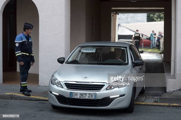 A police vehicle drives out of a building after five people including one child were killed when a fire tore through an apartment in Pau southwestern...