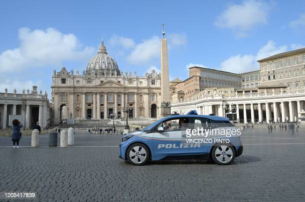 A police vehicle drives past a deserted St Peter's square at the Vatican on March 6 2020 The Vatican on March 6 reported its first coronavirus case...