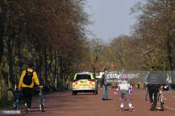 A police vehicle is driven on patrol as people enjoy the sunshine in Greenwich Park in London on March 26 2020 after the government ordered a...