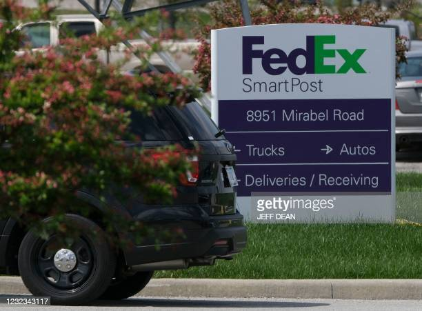 Police vehicle is parked at the entrance of the site of a mass shooting at a FedEx facility in Indianapolis, Indiana, April 16, 2021. - A gunman has...
