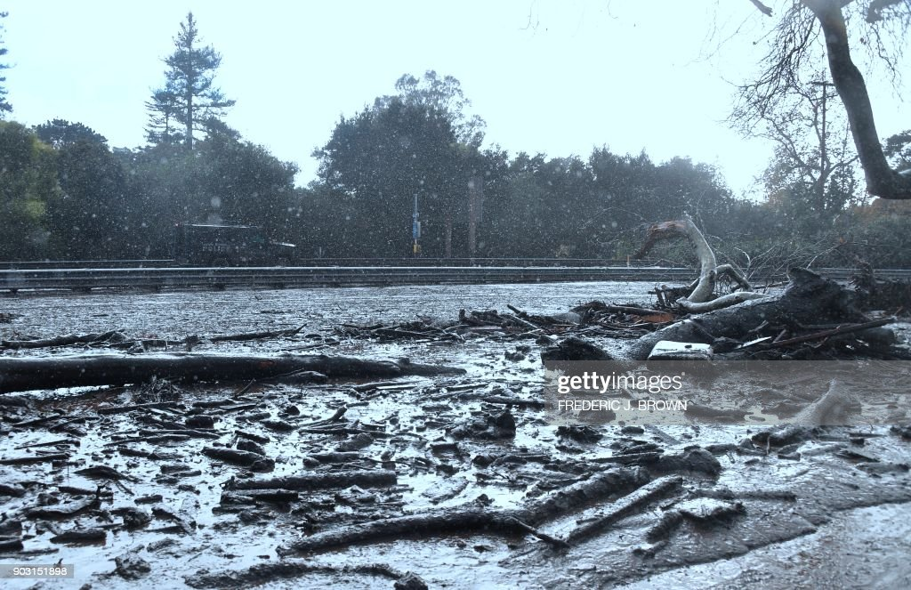 A police vehicle makes its way in the rain along a closed off section of US Hwy 101 flooded after mud and debris broke through an embankment along the freeway near the San Ysidro exit in Montecito, California on January 9, 2018. Mudslides unleashed by a ferocious storm demolished homes in southern California and killed at least 13 people, police said Tuesday. /