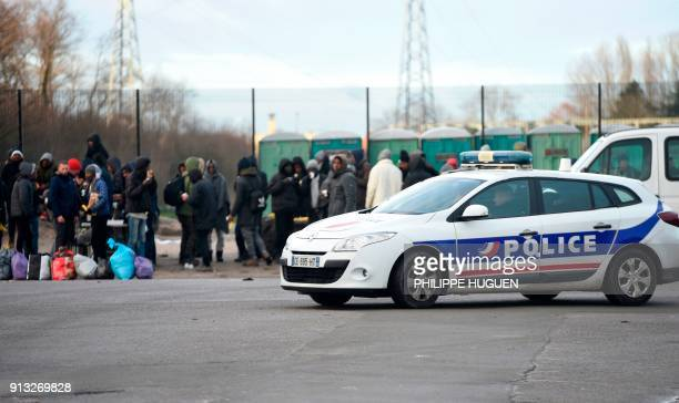 A police vehicle passes by people gathering in Calais northern France on February 2 a day after a large brawl between a hundred migrants resulted in...