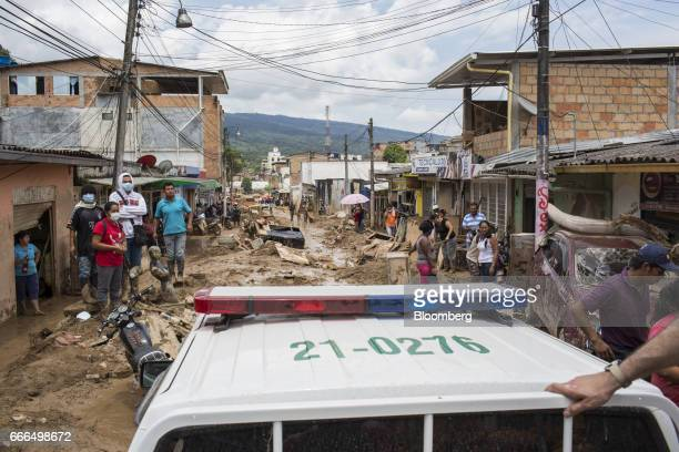 A police vehicle sits on a destroyed road as displaced residents inspect damage in the Prospero neighborhood of Mocoa Putumayo Colombia on Monday...