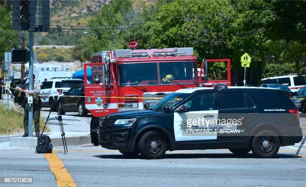 A police vehicle stands at a closedoff street outside the North Park Elementary School in San Bernadino California on April 10 2017 after a gunman...