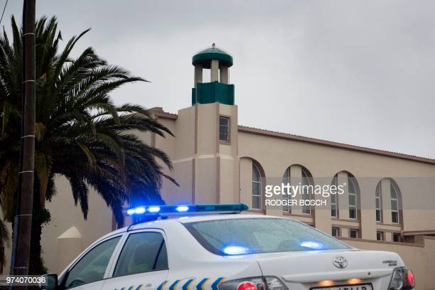 A police vehicle stands in front of the mosque following a stabbing attack that left two worshippers dead and the attacker shot by the police on June...