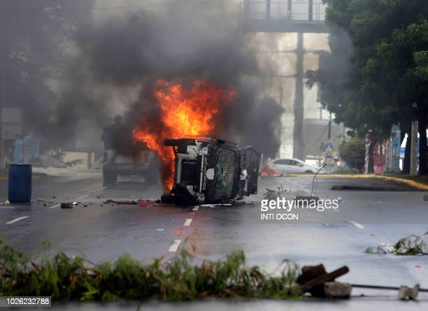 A police vehicle which was overturned and set on fire by demosntrators remains amid the street after an antigovernment protest in Managua on...