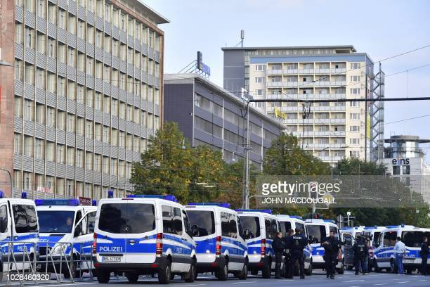 "Police vehicles are parked in a row near during a counter demonstration called ""We stay - antifascist active"" against a rally organised by the..."