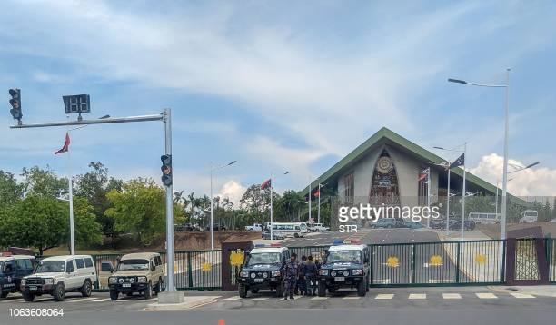 Police vehicles are pictured at the front entrance of Papua New Guinea's parliament in Port Moresby on November 20 2018 Police and soldiers stormed...