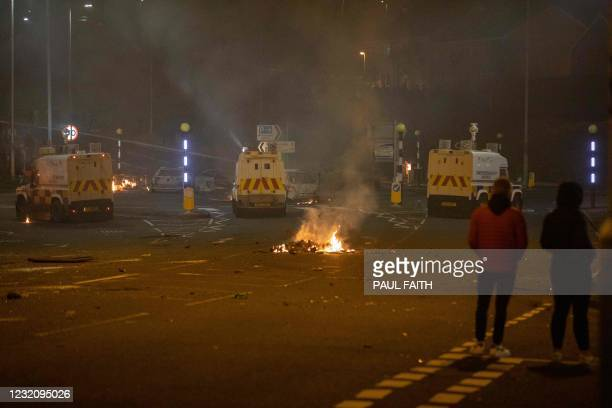 Police vehicles are positioned at the scene of violence in Newtownabbey, north of Belfast, in Northern Ireland on April 3, 2021. - The disturbance in...