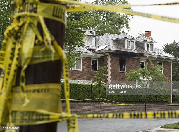 Police vehicles are seen outside a firedamaged home where four people were killed last week in Washington DC May 21 2015 Police were on the hunt...