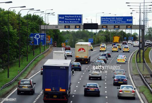 Police vehicles form as escort as drivers take part in a goslow convoy on the M60 motorway near Manchester in north west England on May 8 2011...