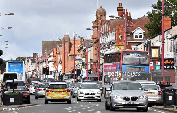 Police vehicles join Saturday morning traffic on Soho Road in the Handsworth area of Birmingham, central England on August 22 as Britain's...