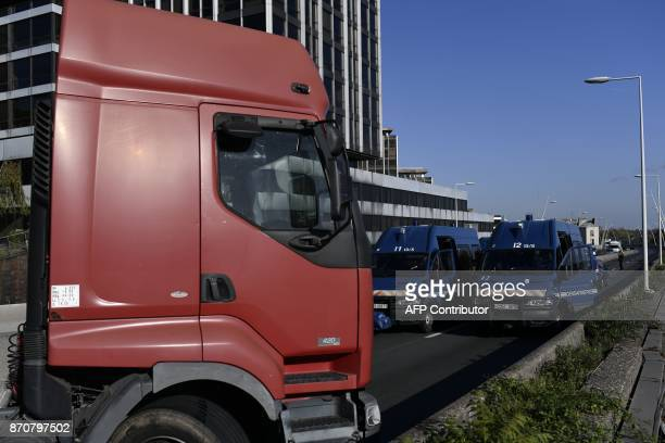 Police vehicles stop trucks from stallholders blocking the A13 highway during a goslow operation in SaintCloud in the outskirts of Paris to protest...