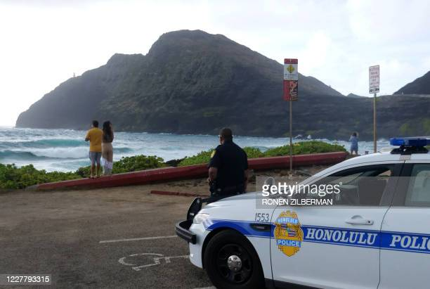 Police wait for people to return to their cars before closing the beach parking lot in preparation for Hurricane Douglas, in Honolulu, Hawaii, on...