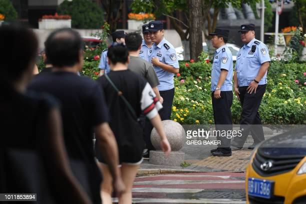 Police wait to check the identification of passersby as they search for petitioners near China's Banking Regulatory Commission in Beijing on August 6...