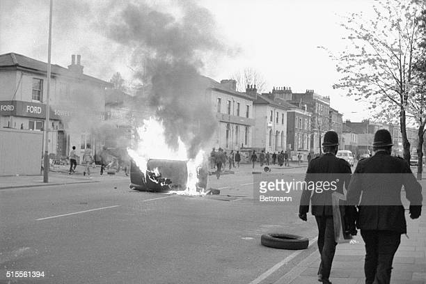 Police walk along street in Brixton area of south London past a burning car Rioting looting and arson confronted police in the area's second...