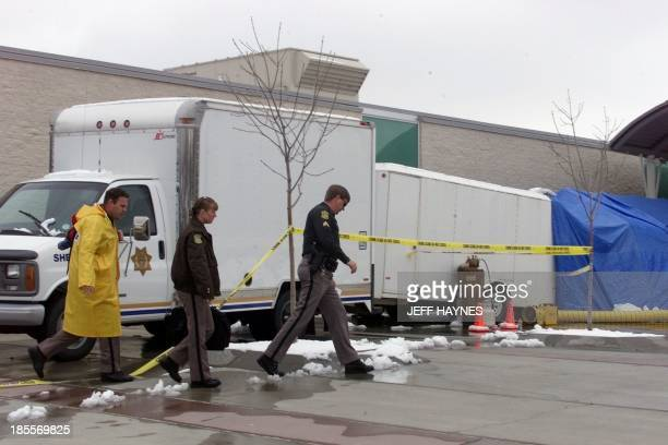 Police walk by the evidence trailer in front of Columbine High School in Littleton CO 22 April the site where fourteen students and one teacher were...