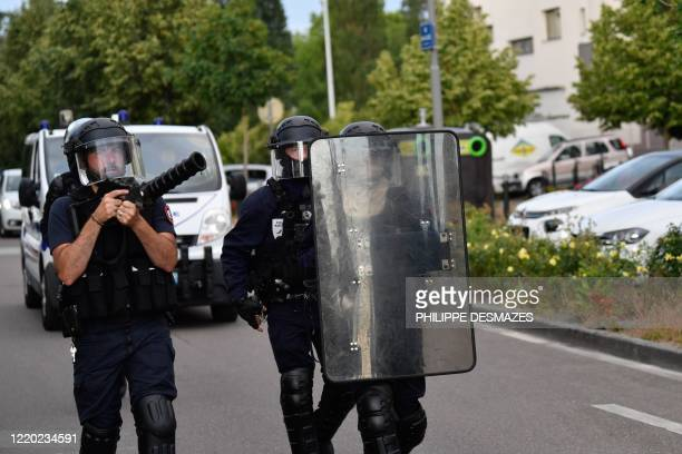 Police walk carrying a shield and a tear gas canister launcher in the Gresilles area of Dijon, eastern France, on June 15 as new tensions flared in...
