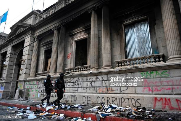 Police walk in front of the Congress a day after it was patrly burned during a protest demanding the resignation of Guatemalan President Alejandro...