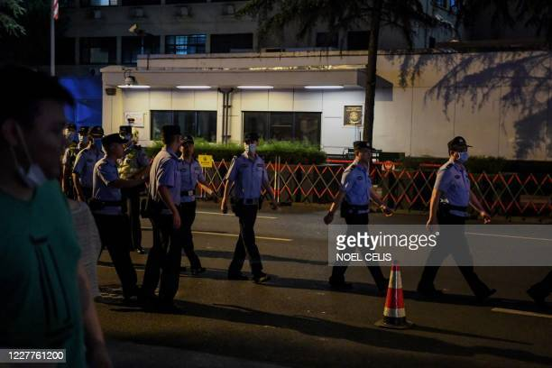 Police walk in front of the entrance of US consulate in Chengdu, southwestern China's Sichuan province, on July 24, 2020. - China on July 24 ordered...