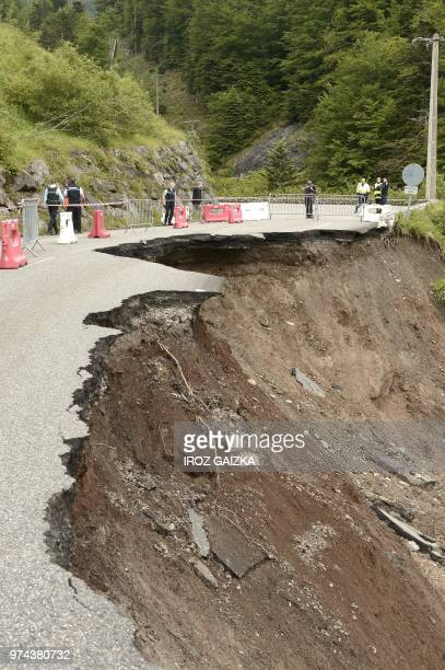 Police walk near a damaged road after a landslide due to a heavy rainfall on June 14 2018 near Laruns southwestern France Tis road is part of the...