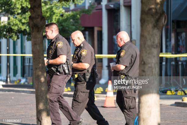 Police walk near the scene after an active shooter opened fire in the Oregon district in Dayton Ohio on August 4 2019 Nine people were killed in a...