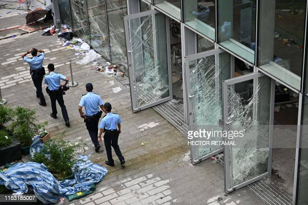 Police walk next to the Legislative Council building in Hong Kong on July 2 a day after protesters broke into the building Hong Kong's leader on July...