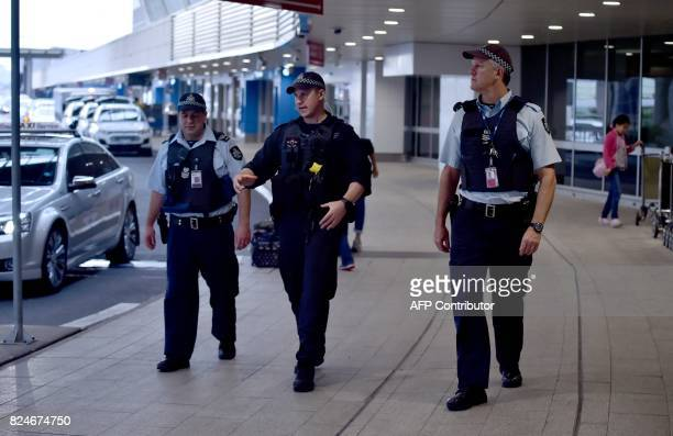 Police walk outside the international terminal as they patrol Sydney Airport on July 31 2017 Four men accused of plotting to bring down a plane from...